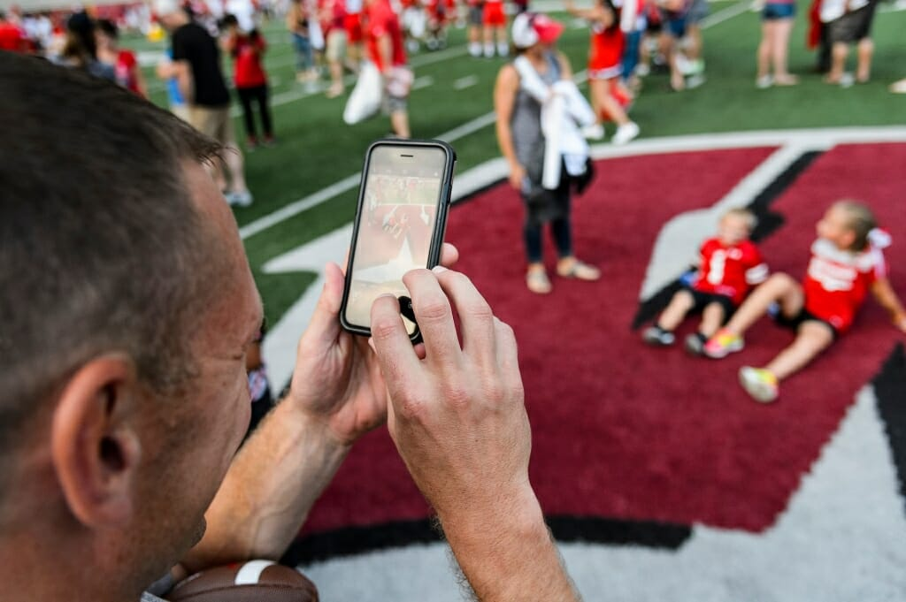 Ryan Koch takes a picture of his children Mason, 4, and Kaylie, 8, sitting on the motion W logo at center field during Football Family Fun Day at Camp Randall Stadium on Aug. 1.