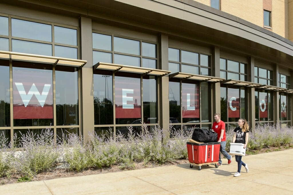 Photo: Student pushing red laundry cart in front of large building windows