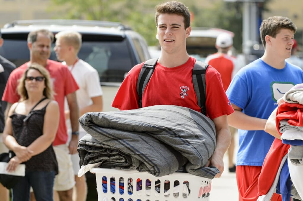 Photo: Male student carrying laundry basket with blanket on top