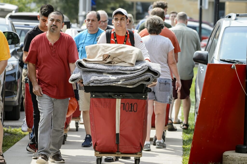 Photo: Student pushing red laundry cart overflowing with things