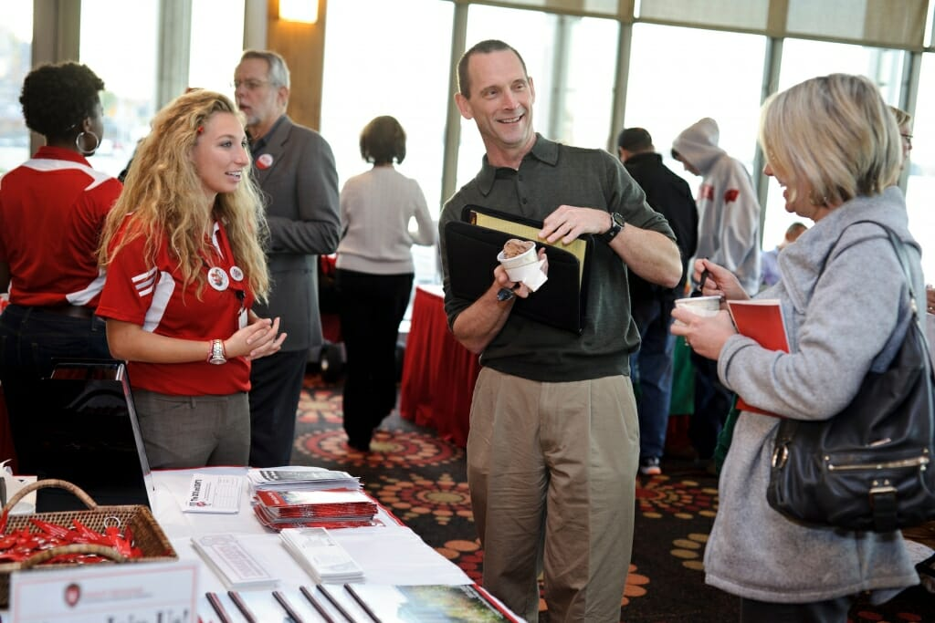 Photo: Conference volunteer talking with attendees at table