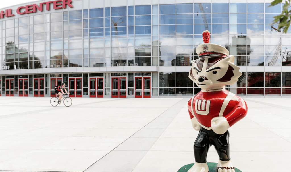 """...And On Wisconsin!"" stands outside of the Kohl Center. The Bucky statue is dressed in UW Marching Band attire and is doing the signature marching step of the band."