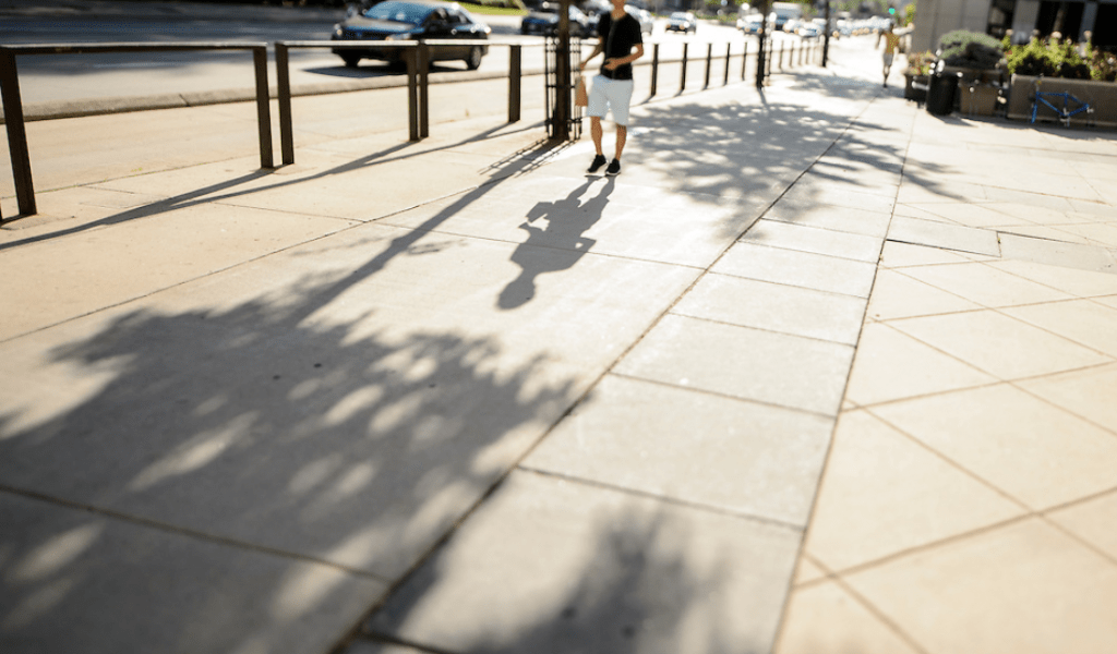 A passing pedestrian casts a shadow on a sidewalk along University Avenue near Grainger Hall of the University of Wisconsin–Madison campus as the sun rises during a summer morning.