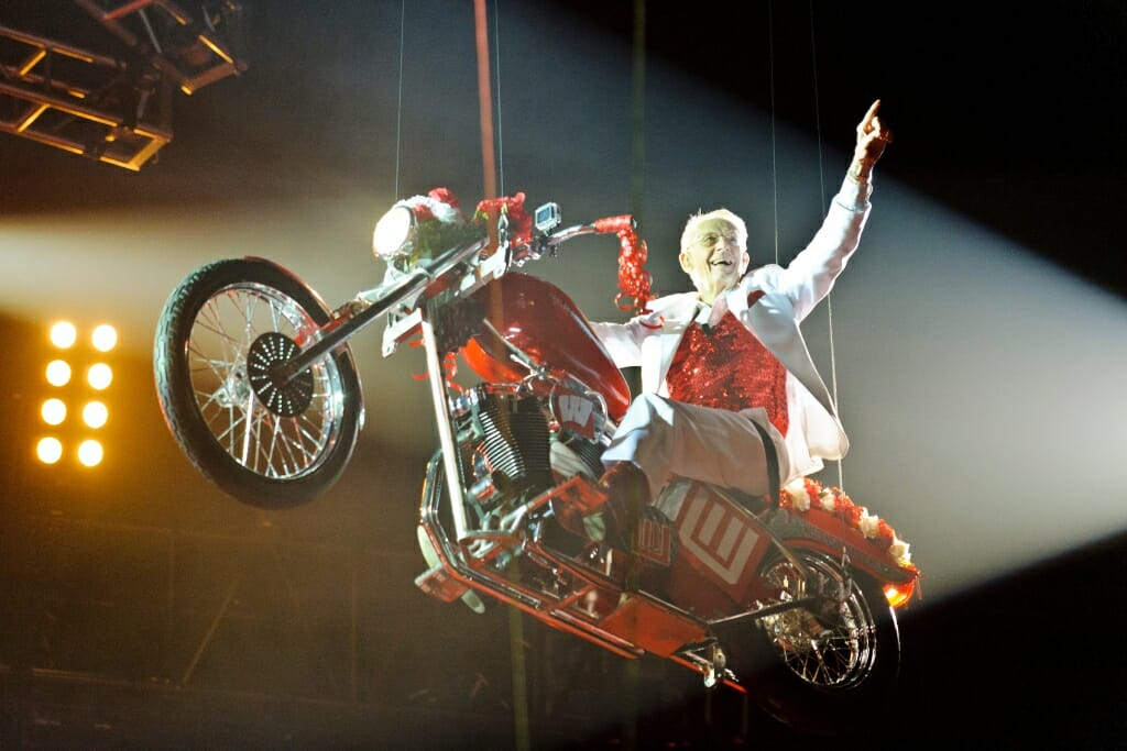 Photo: Leckrone suspended on motorcyle, waving to audience