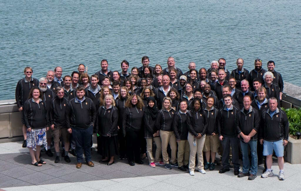 Photo: Large group of employees standing with lake in background