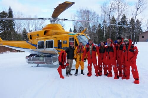 Photo: People in jumpsuits standing in front of helicopter in the snow