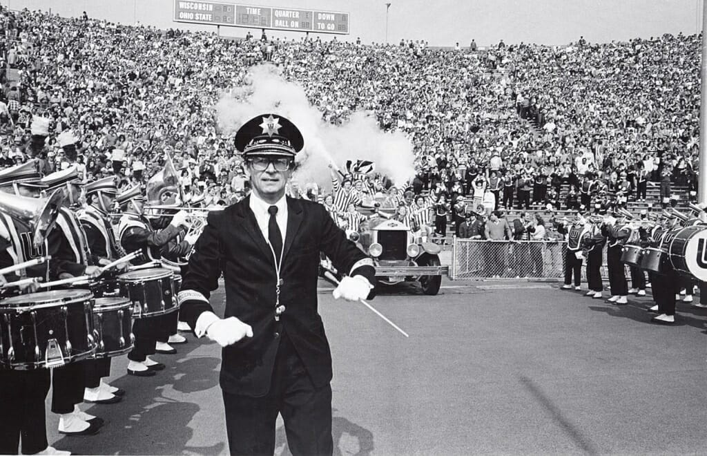 Photo: Leckrone conducting while Bucky Wagon enters stadium behind him