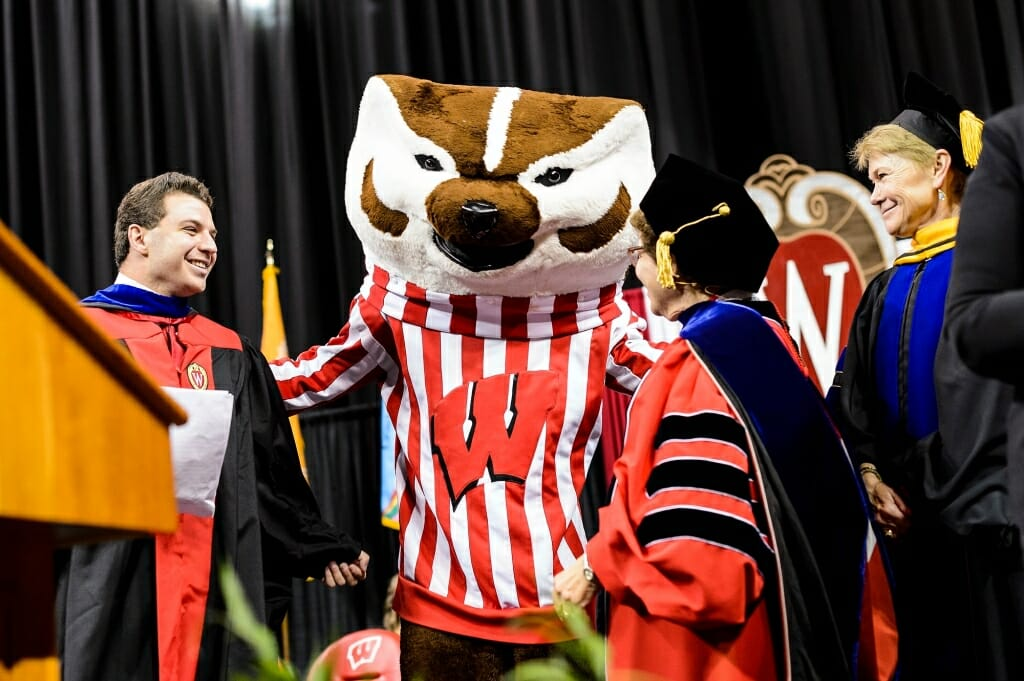 From left to right, undergraduate student speaker Yogev Ben-Yitschak, Chancellor Rebecca Blank, and Provost Sarah Mangelsdorf welcome UW-Madison mascot Bucky Badger to the stage at the end of the ceremony.