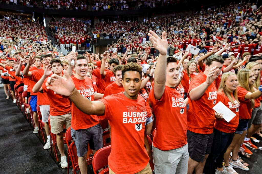 """Photo: Students, some in """"Business Badger"""" t-shirts, standing in crowd waving arms"""