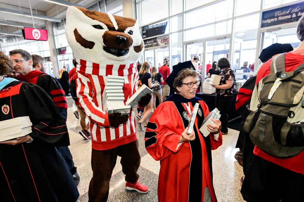 Photo: Bucky Badger standing behind Rebecca Blank holding a stack of books