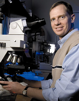 Photo: David Gamm sitting by a microscope