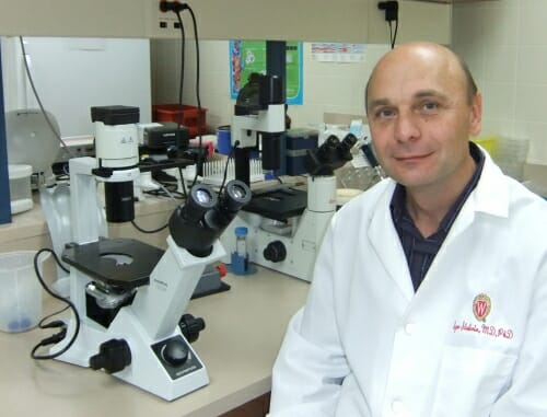 Photo: Igor Slukvin in white lab coat sitting next to mircroscope