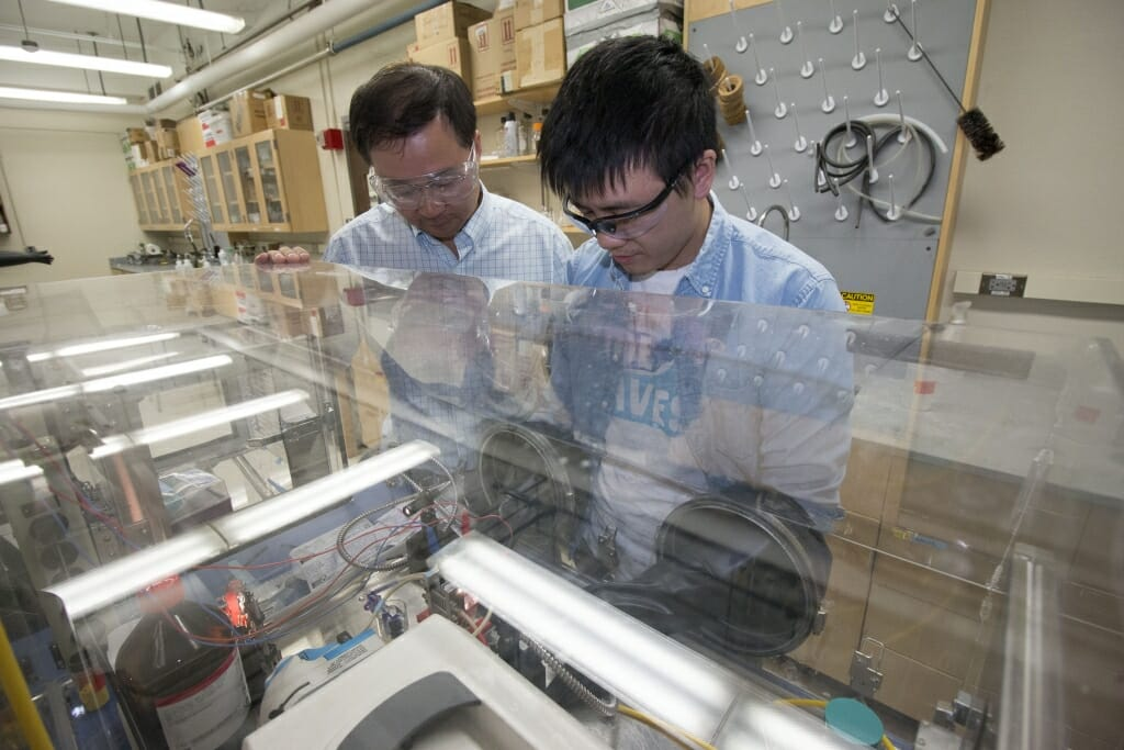 Photo of Song Jin, left, and graduate student Wenjie Li observing their lab-scale device for storing and releasing solar energy.