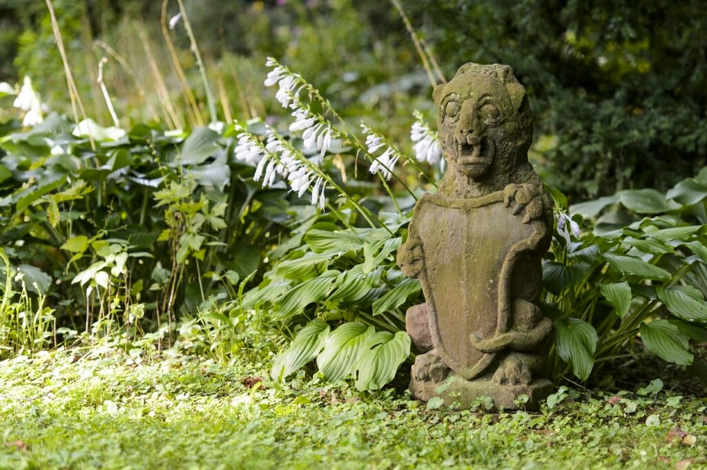 Photo: Stone gargoyle sitting in garden in front of hostas