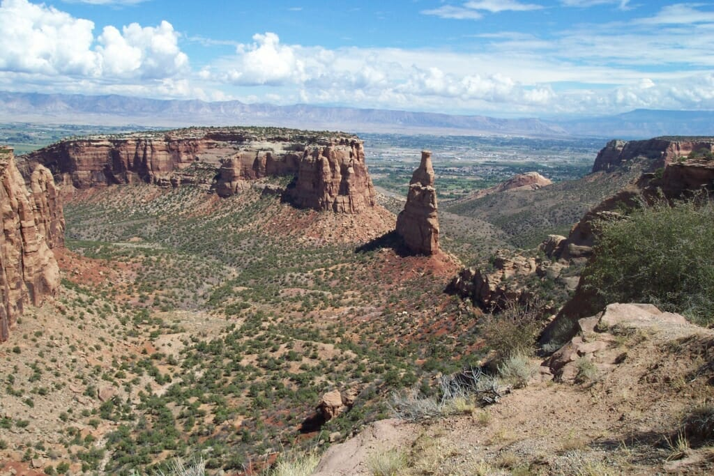 Colorado National Monument AltText: towers and mesas of brown rock in the midground with shrubby desert ground taking up most of the foreground