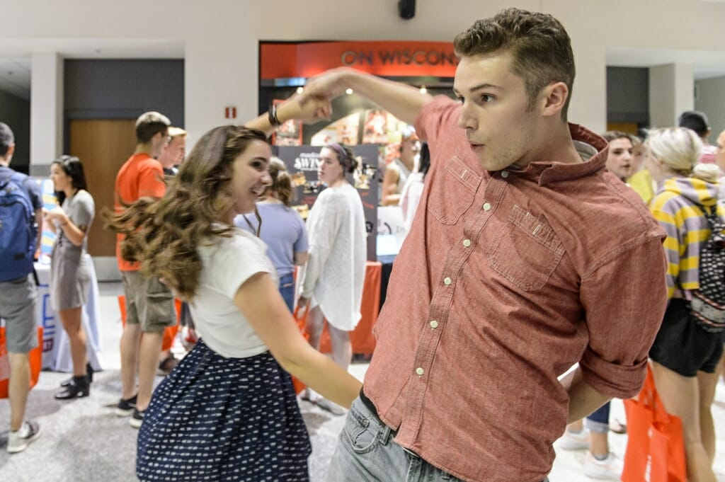 Amy Lossen (left) and Tony Feller (right) give a demonstration near Madison Swing dance club booth.