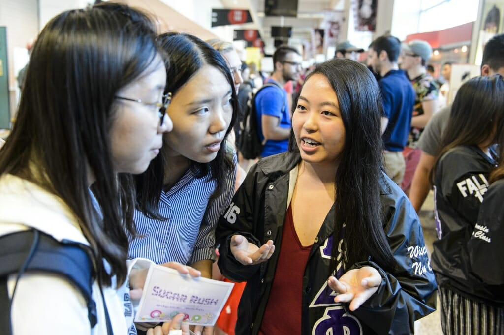 Panouly Moua (right) talks with students about the Alpha Kappa Delta Phi sorority.