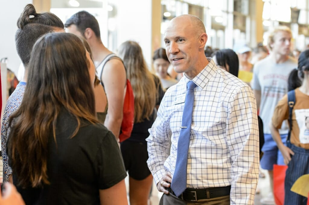 Interim dean of students Argyle Wade (right) talks with a student during the Student Organization Fair.