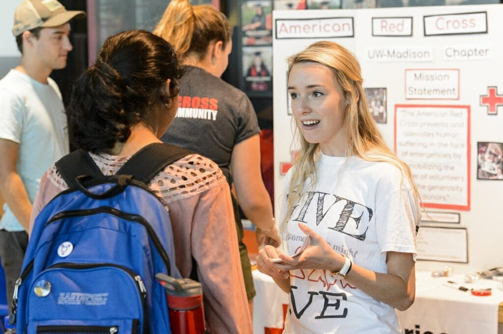 Carly Langkamp (right) speaks to a student about the UW American Red Cross Club.