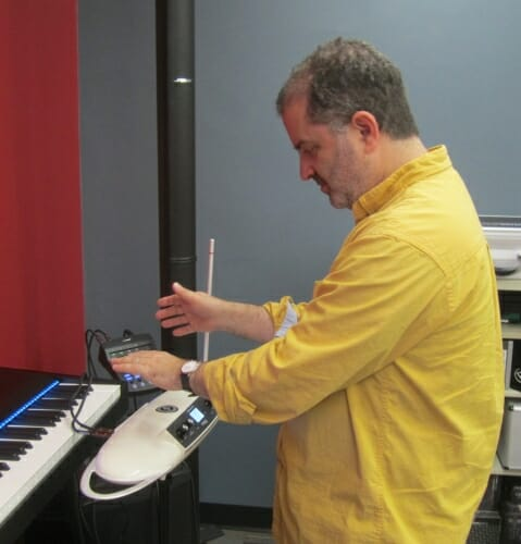 Photo: Professor standing in front of keyboard with theramin