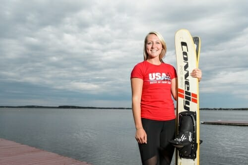 Gabbie Taschwer stands on a dock, holding her water skis, with Lake Mendota in the background.