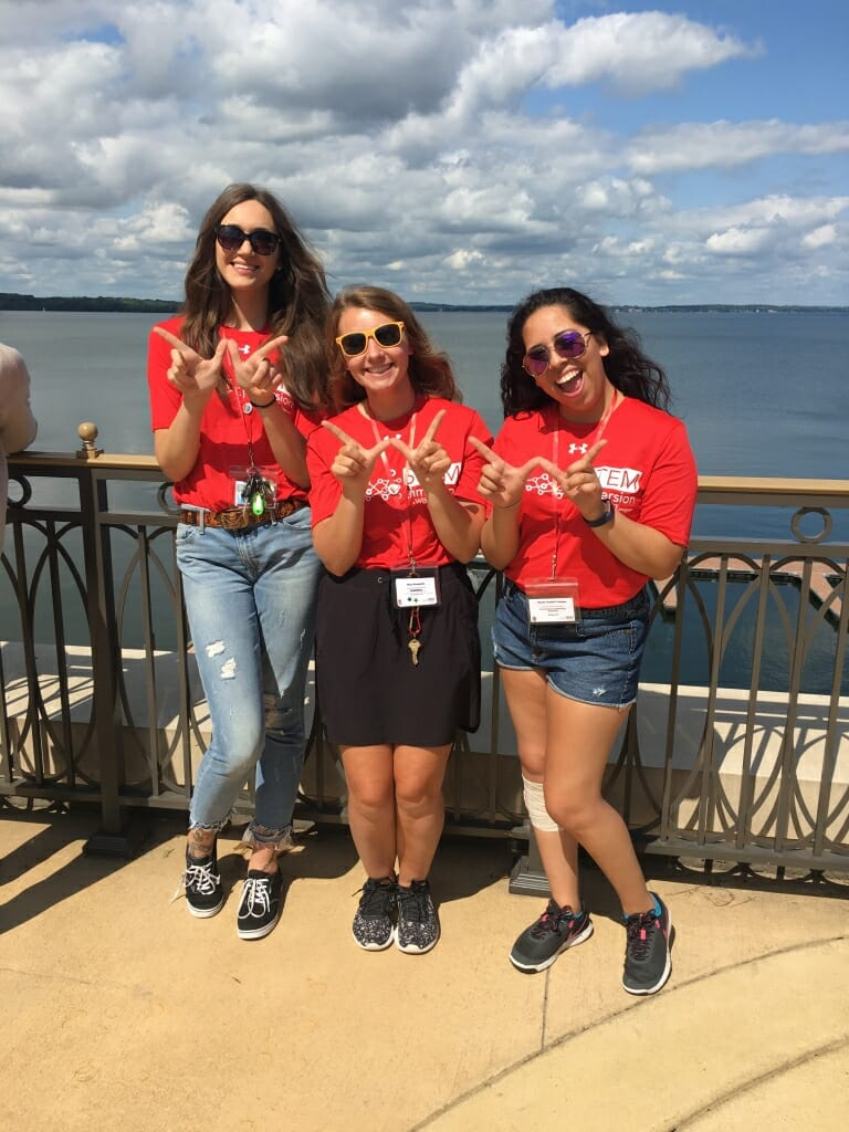 """A photo of three college students holding their hands in the shape of a """"W"""" for Wisconsin."""