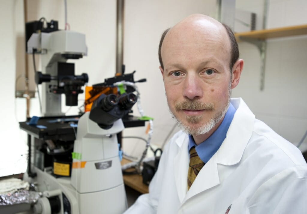 Photo of Tim Kamp wearing a white coat by a microscope.