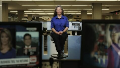 Photo: Laura Helmuth sitting on a stool between TV monitors showing news programs
