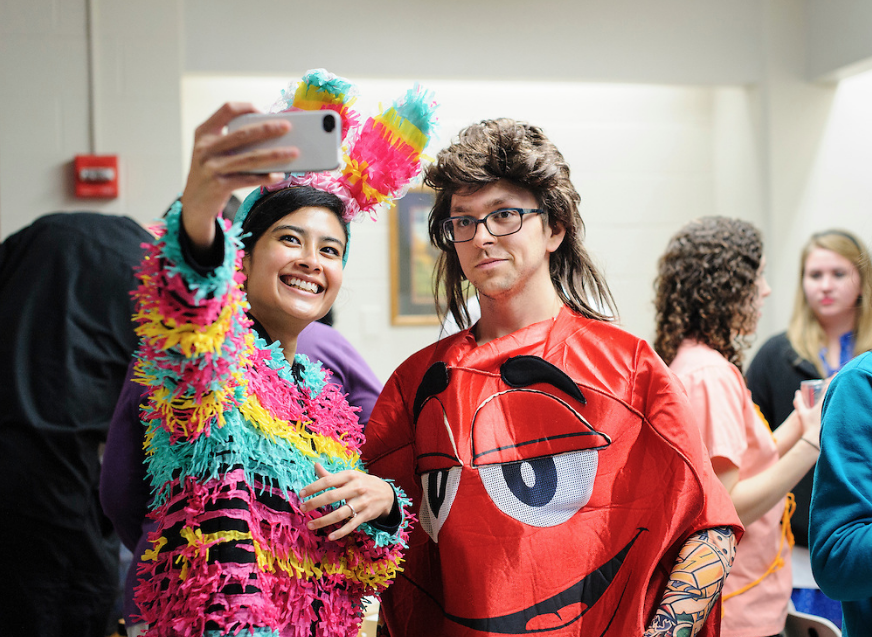 Two residents take a selfie for Halloween. One is dressed as a pinata and the other is dressed as an M&M.