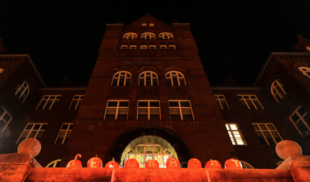 "A row of displayed pumpkins -- each carved with a letter -- spell out the word ""geography"" outside Science Hall at the University of Wisconsin–Madison during a pre-Halloween, autumn night on Oct. 28, 2016."