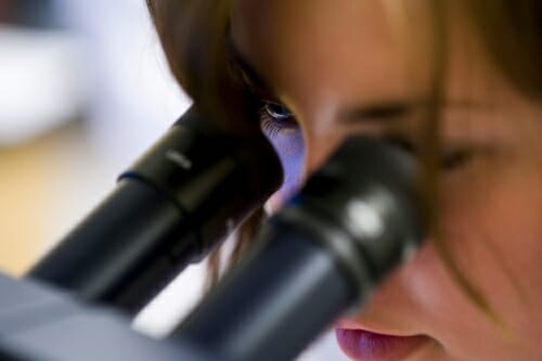 Woman peers into microscope.