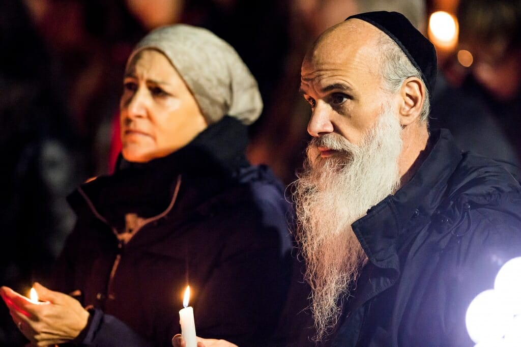 Photo of Rabbi Gairshon Vogel holding a candle.