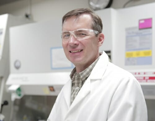 Photo: Sean Palecek in a lab wearing safety goggles and a white lab coat