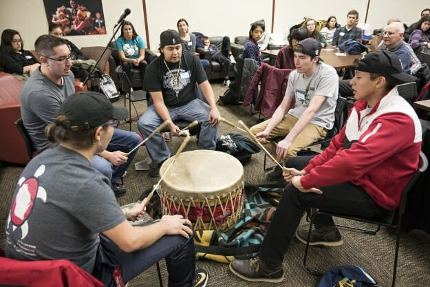 A number of students sit around a Native drum and bang it.