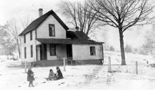 Black and white photo of Signe with her sisters in the snow in front of the family farmhouse.