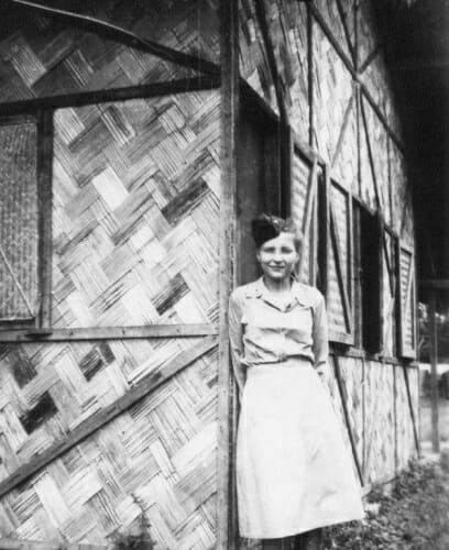 Black and white photo of Signe Skott Cooper in front of her basha, the nurse's living quarters at the military hospital in India. It had four rooms for eight nurses with a latrine a half block away.