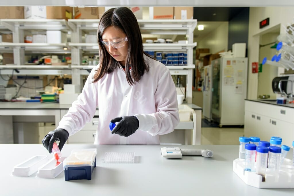 Photo: Xie in white lab coat and rubber gloves holding a sample at a lab bench