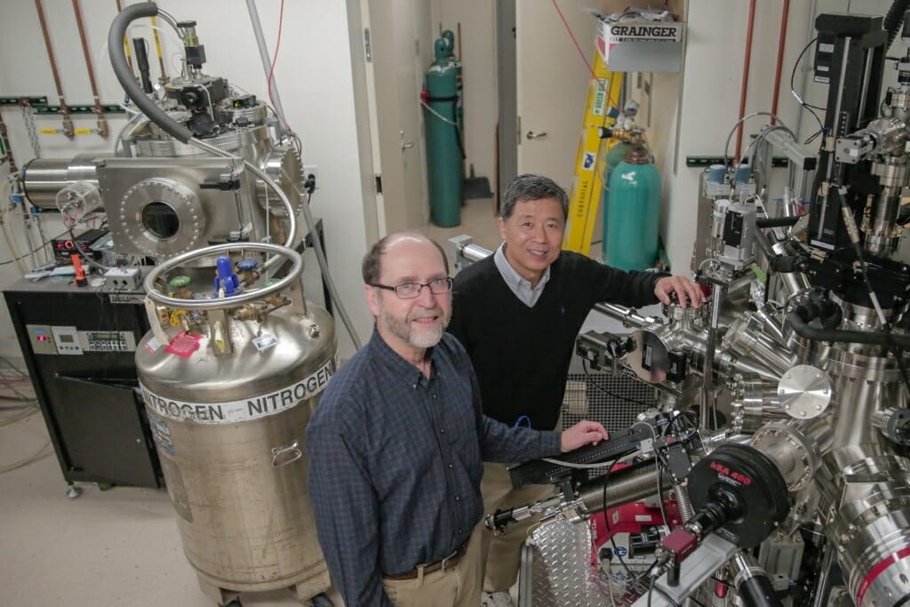Photo: Chang-Beom Eom, right, and Mark Rzchowski inspect a materials growth chamber.