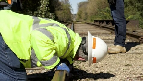 Photo: Worker in hardhat crouching and looking down track