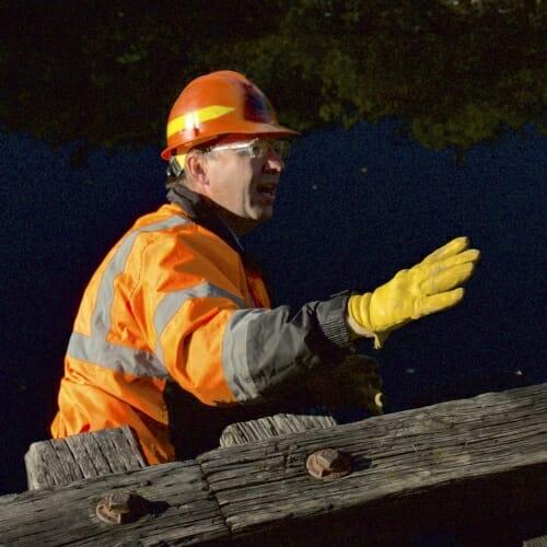 Photo: Man in hardhat standing under rails