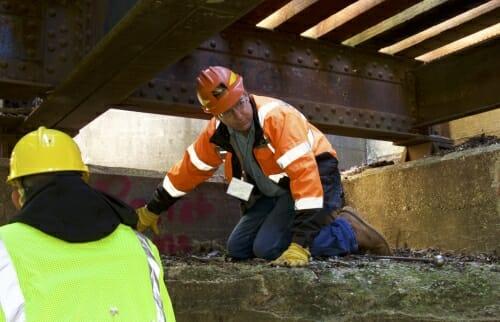 Photo: Man in hardhat under rail ties on bridge
