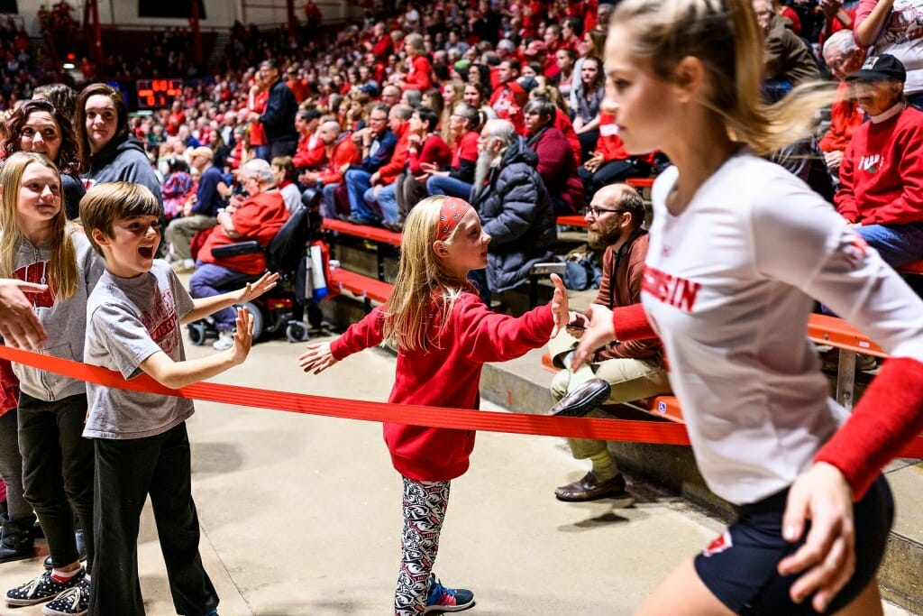 Volleyball team members jog out onto the court and high-five a young fan.