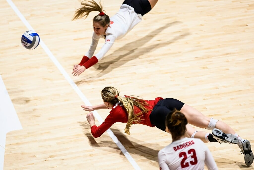 Two Wisconsin players simultaneously dive for a ball.