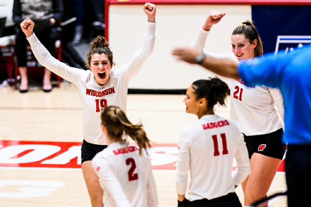M.E. Dodge, wearing No. 19, lifts her arms in celebration as other players look on in jubilation after a good point.