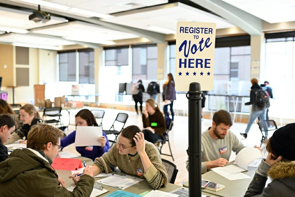 "Photo: Students sitting at tables filling out forms, under a sign that says ""Vote Here."""