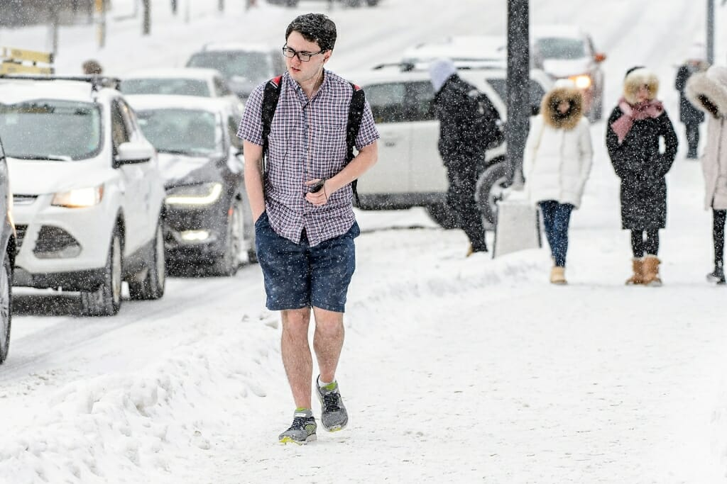 Photo: Student walking in shorts and short-sleeve shirt in snow