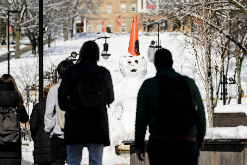 Photo: People looking at snowman with orange construction cone on head