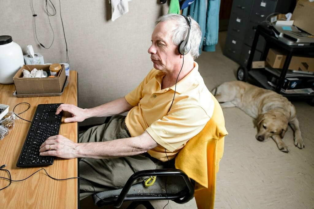 Photo: Man sitting at computer with headphones on and dog on floor behind