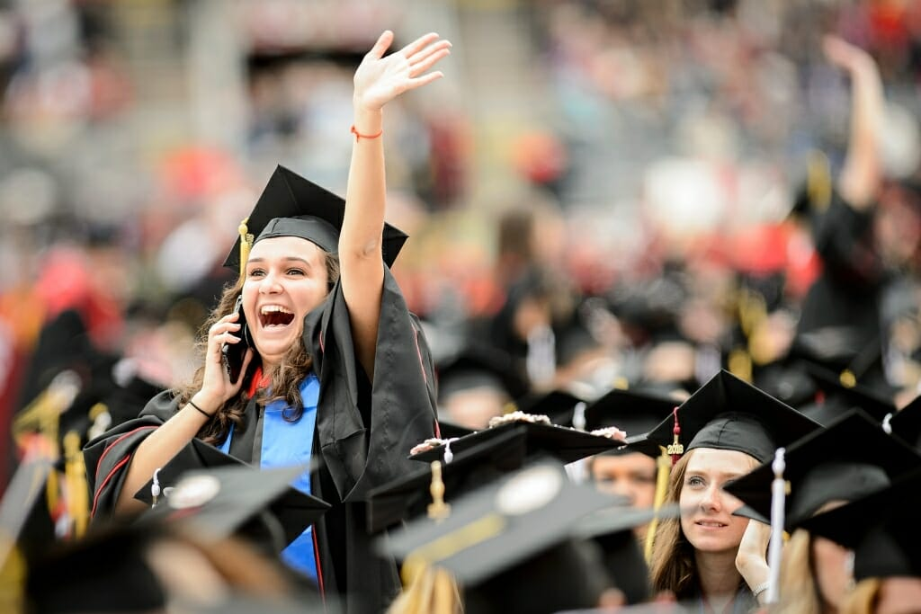 Photo: Student in cap and gown waving and talking on phone