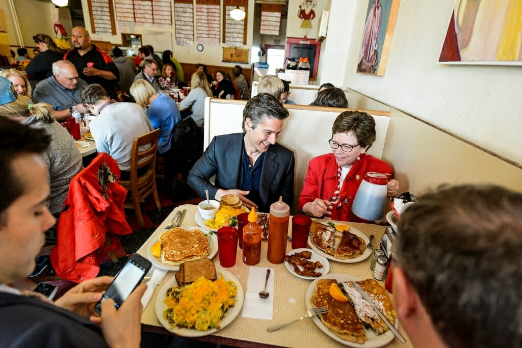 Photo: David Muir and Rebecca Blank sitting in restaurant booth with plates of food